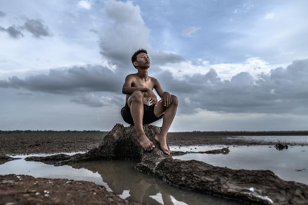 Een man zat gebogen zijn knieën, kijkend naar de lucht aan de voet van de boom en omringd door water.