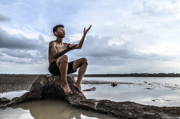 Een man zat op zijn knieën, maakte een handsymbool om regen te vragen aan de boombasis en omringd door water.