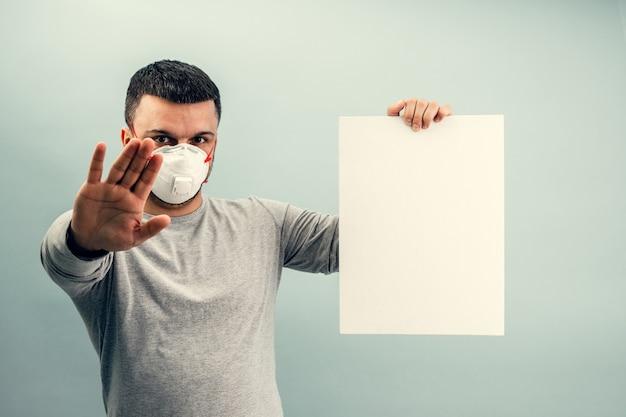 Een man zet een beschermend masker op. ademhalingsbescherming tegen coronavirus. persoonlijke beschermingsmiddelen voor een pandemie van een virale infectie. covid-19. kopieer ruimte
