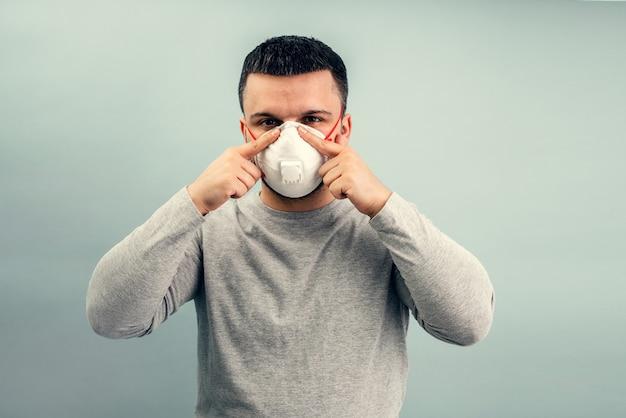 Een man zet een beschermend masker op. ademhalingsbescherming tegen coronavirus. persoonlijke beschermingsmiddelen voor een pandemie van een virale infectie. covid-19.