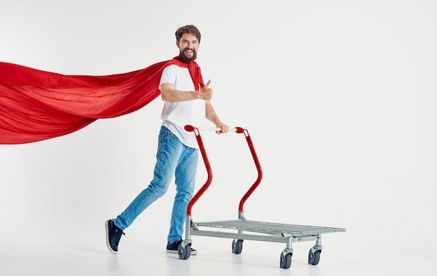 Een man zij met een rood tafelkleed en een kar in de vorm van superman