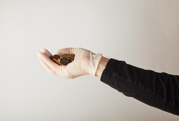 Een man zijn hand in een witte medische handschoen houdt geld in de vorm van kleine munten. bescherming tegen virussen en bacteriën. concept. covid-19 of coronavirus