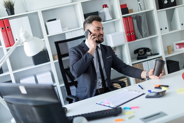 Een man zit aan de balie op kantoor, aan de telefoon te praten en een glas koffie in zijn hand te houden.