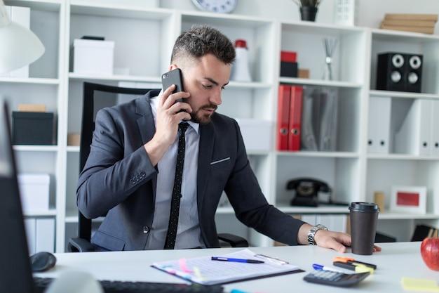 Een man zit aan de balie op kantoor, aan de telefoon te praten en een glas koffie vast te houden.