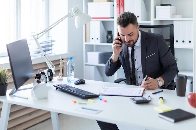 Een man zit aan de balie op kantoor, aan de telefoon te praten en een marker in zijn hand te houden.