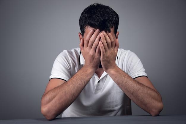 Een man zit aan de tafel en bedekt zijn gezicht van vermoeidheid op een grijze muur