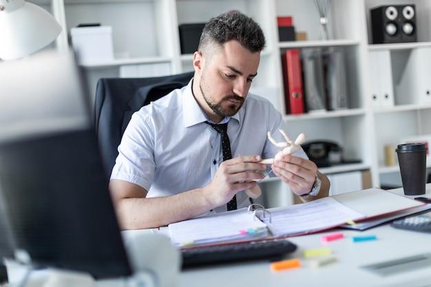 Een man zit aan een tafel op kantoor en kijkt naar een houten man.