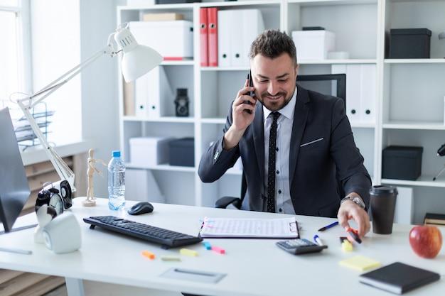 Een man zit aan het bureau op kantoor, praat aan de telefoon en neemt een stift in zijn hand