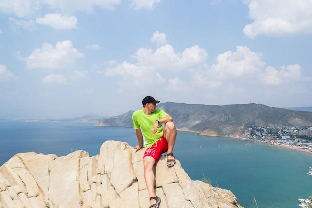 Een man zit bovenop een berg en kijkt naar de zee