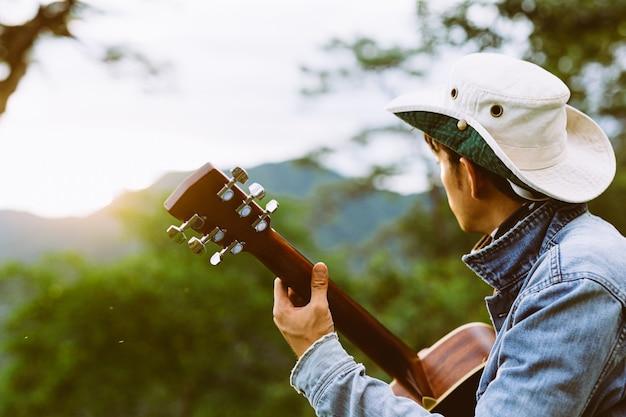 Een man zit gelukkig gitaar spelen in het bos alleen.