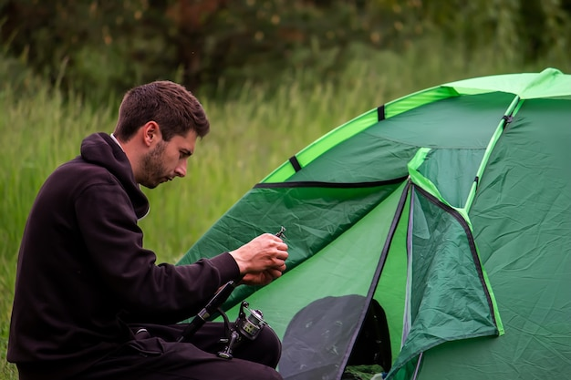 Een man zit in de buurt van een toeristentent. natuur, recreatie, kamperen. selectieve focus