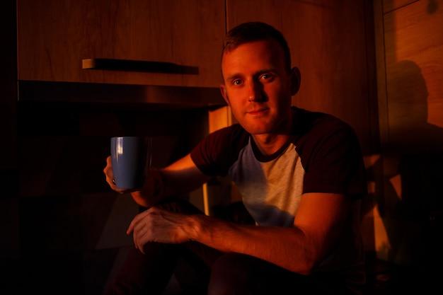 Een man zit in de keuken in het licht van de zonsondergang en drinkt koffie