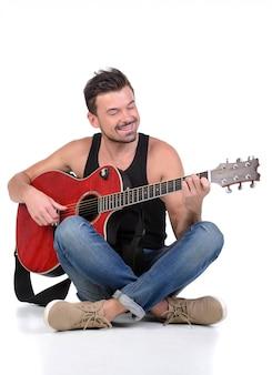 Een man zit in de lotushouding en speelt gitaar.