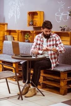 Een man zit in een café en werkt op een laptop.