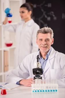 Een man zit in een laboratorium