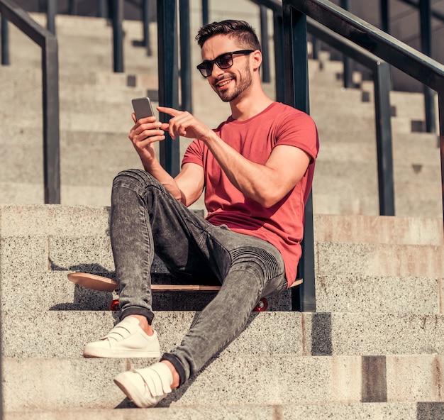 Een man zit op de trap en kijkt in de telefoon.