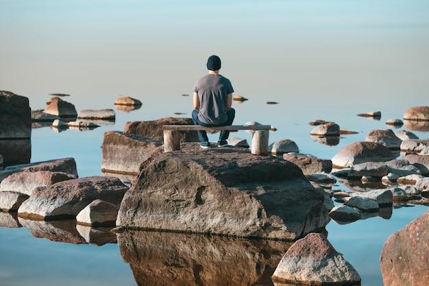 Een man zit op een houten bank en bewondert het landschap.