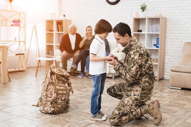Een man zit op één knie en neemt afscheid van zijn zoon.