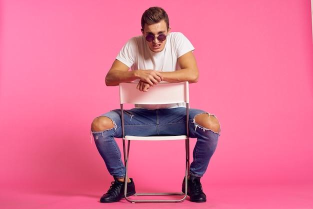 Een man zit op een stoel in een wit t-shirt en jeans moderne stijl roze geïsoleerde ruimte