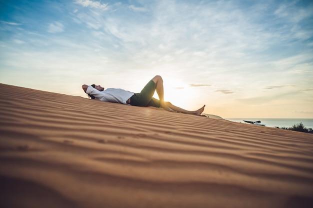 Een man zit op het zand in de woestijn