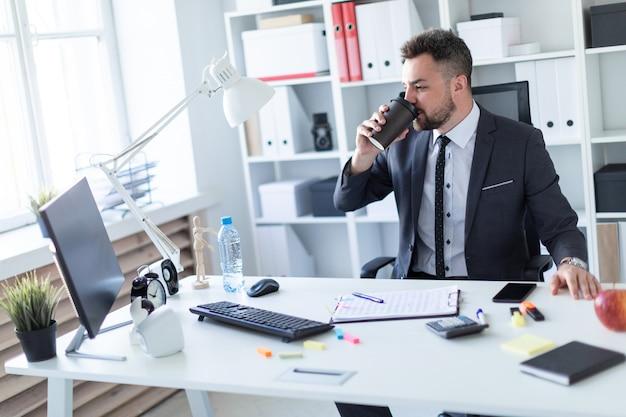 Een man zit op kantoor aan de tafel, drinkt koffie en kijkt naar de monitor.