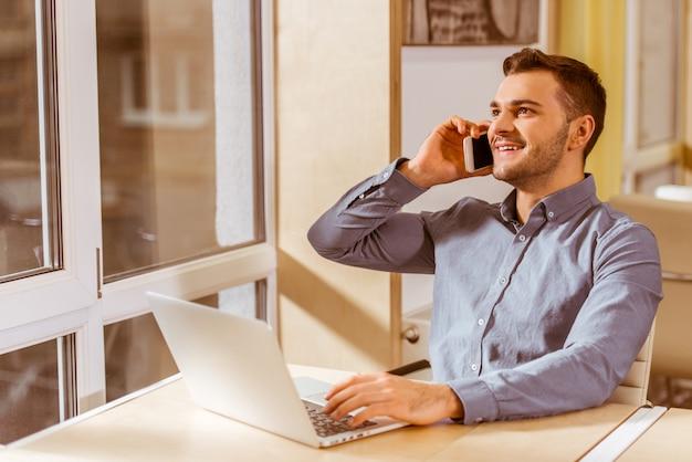 Een man zit op kantoor aan de telefoon te praten en te werken.