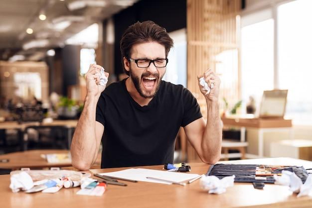 Een man zit op kantoor en schreeuwt van zijn werk.