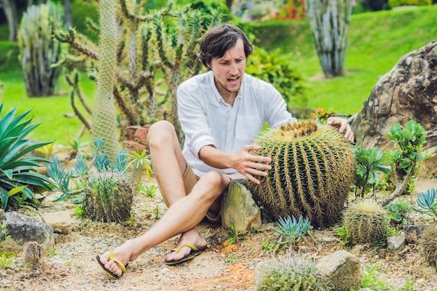 Een man zit tussen grote cactussen