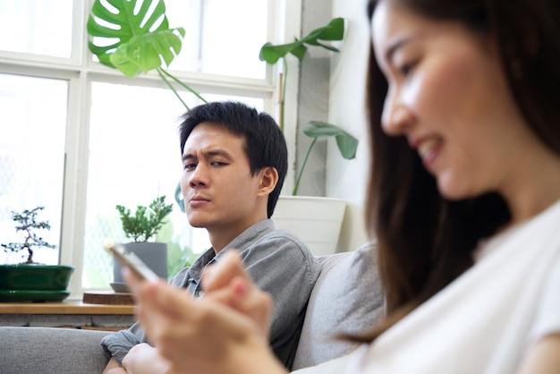 Een man zittend op de bank voelt zich niet gelukkig met zijn vriendin, terwijl ze graag gebruikmaakt van de telefoon