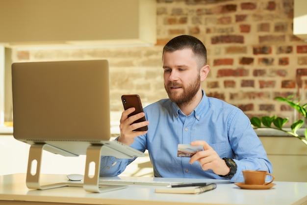 Een man zoekt online verkoop op een smartphone, met een creditcard in zijn hand voor de computer thuis