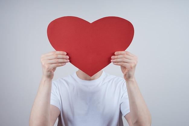 Een man zonder gezicht, een gezicht bedekt met een papieren hart