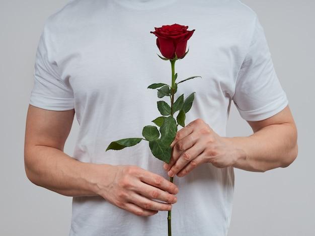 Een man zonder gezicht in een wit t-shirt, met een rode roos vast