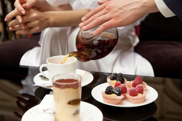 Een man zorgt voor een vrouw: giet haar groene thee. op de tafel staan toetjes: tiramisu en gebak met verse bessen. zonder gezichten, in het kader van de hand. detailopname