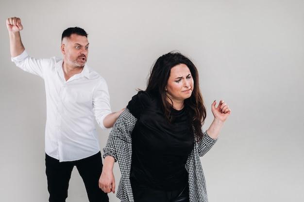 Een man zwaait met zijn hand naar een mishandelde vrouw die op een grijze achtergrond staat. huiselijk geweld.