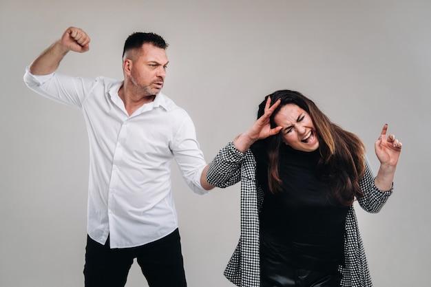 Een man zwaait met zijn vuist naar een mishandelde vrouw die op een grijze achtergrond staat. huiselijk geweld