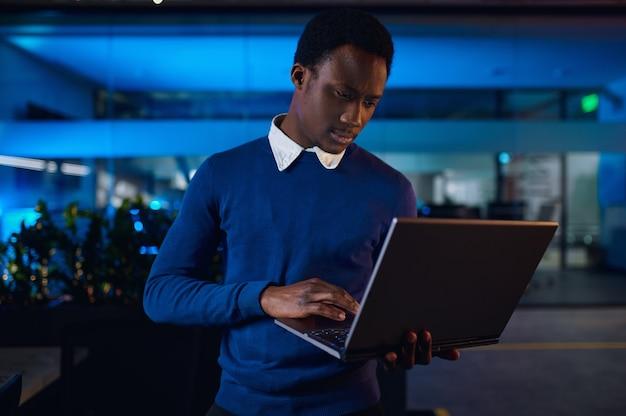 Een manager werkt op laptop in nachtkantoor. mannelijke werknemer, donker zakencentrum interieur, moderne werkplek
