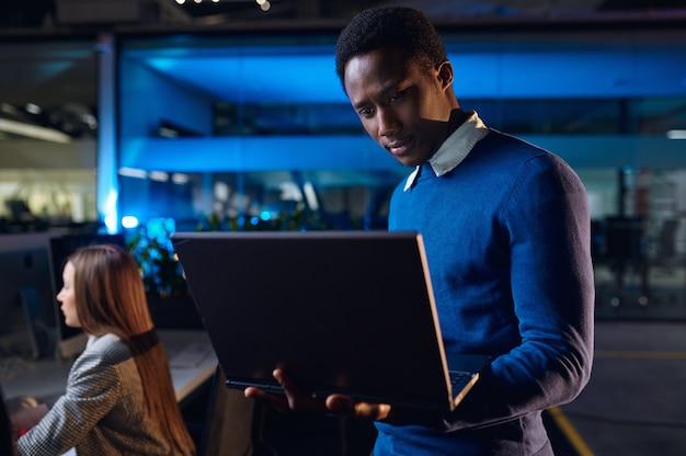 Een manager werkt op laptop in nachtkantoor. mannelijke werknemer, donker zakencentruminterieur, moderne werkplek