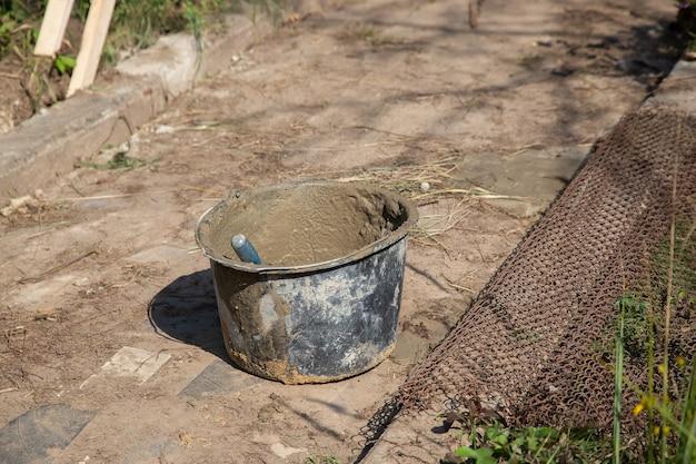 Een mand gevuld met zand en droog cementmengsel staat op het pad in de tuin