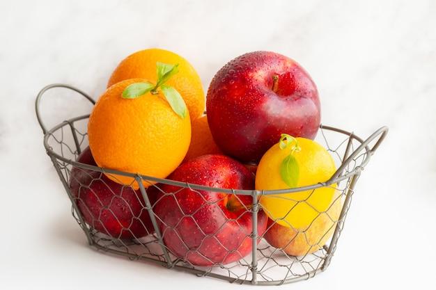 Een mand met fruit. een set vitamines. een metalen mand met appels en sinaasappels. vitamine c. citroen. vegetarisch, veganistisch eten. goede voeding. koolhydraten. een gezonde set. citrusvruchten. appels.