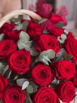 Een mand met heldere rode rozen en eucalyptus op een stoel in een bloemenwinkel. een mooi boeket bloemen voor de vakantie. achtergrond voor de ansichtkaart