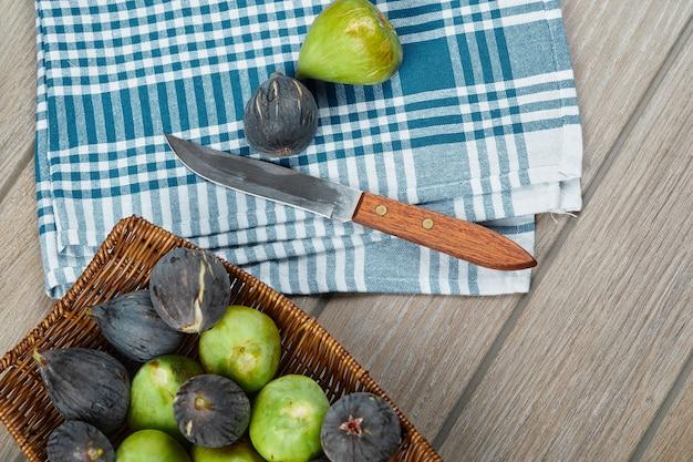 Een mand met rijpe vijgen op houten tafel met een mes en een tafellaken.