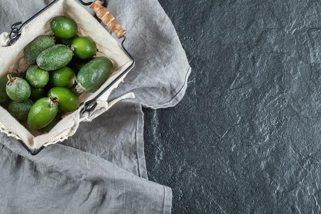 Een mand vol feijoa op een grijs tafelkleed.