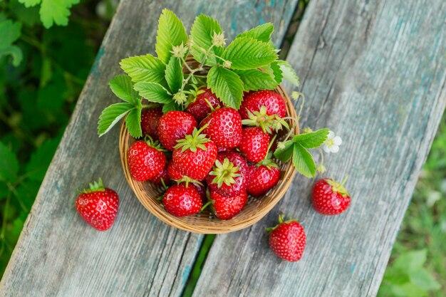 Een mandje met rode sappige aardbeien op rustieke houten tafel