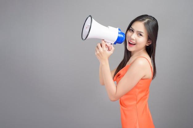 Een manierportret van mooie vrouw die oranje kleding draagt, gebruikt megafoon die over grijze studio als achtergrond wordt geïsoleerd