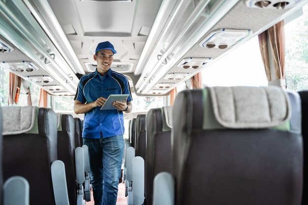 Een mannelijk buspersoneelslid gebruikt een digitale tablet tijdens het controleren van stoelen in de bus