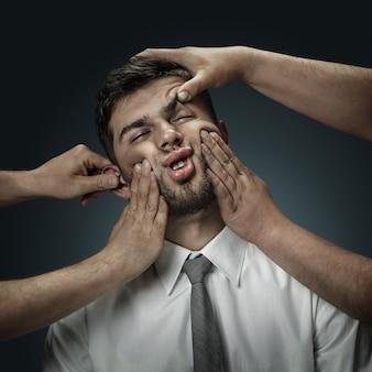 Een mannelijk model omringd door handen als zijn eigen gedachten op een donkere muur. een jongeman twijfelt, kan niet de juiste beslissing kiezen. concept van mentale problemen, problemen op het werk, besluiteloosheid.
