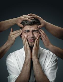 Een mannelijk model omringd door handen als zijn eigen gedachten op een donkere muur