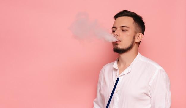 Een mannelijk model rookt waterpijp, sheesha en geniet ervan.