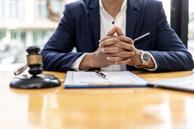 Een mannelijke advocaat zit in zijn kantoor, op een tafel met een kleine hamer om in de rechtszaal op het bureau van de rechter te slaan. en rechtvaardigheidsschalen, stellen advocaten een contract op dat de cliënt kan gebruiken met de beklaagde om te ondertekenen