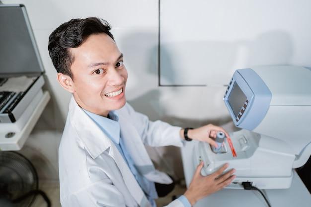 Een mannelijke arts die een oogcomputer in een kamer bij een oogkliniek in werking stelt